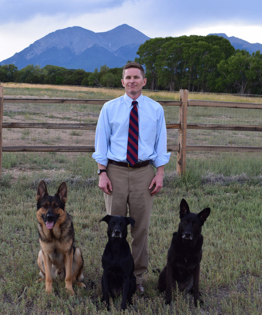 Dan and dogs standing in picturesque landscape